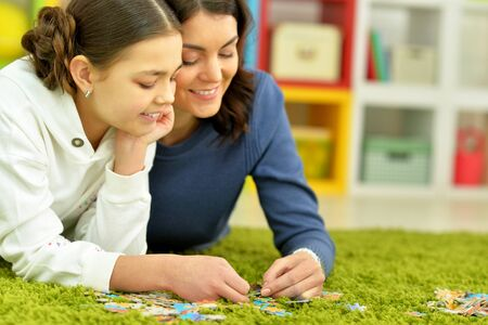 Portrait of mother with little daughter collecting puzzles