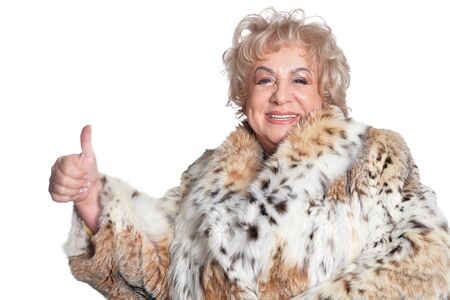 Portrait of beautiful senior woman in fur coat with thumb up