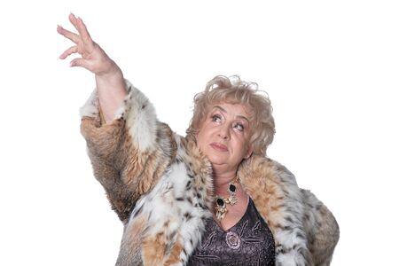 Portrait of beautiful senior woman in fur coat showing something