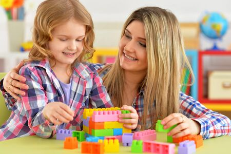 Portrait of little girl and her mother playing colorful plastic blocks together in her room