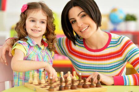 Porträt der schönen jungen Mutter mit ihrer süßen kleinen Tochter, die Schach spielt