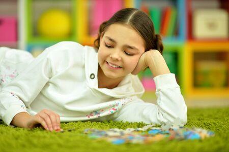 Portrait of cute little girl collecting puzzle pieces Banco de Imagens - 128847802