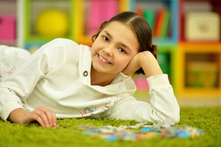 Portrait of cute little girl collecting puzzle pieces Banco de Imagens - 128847803