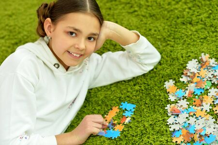 Portrait of cute little girl collecting puzzle pieces