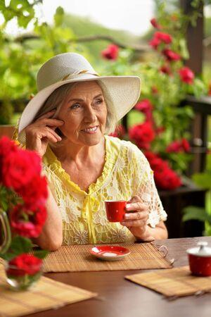 Portrait of cute happy aged woman drinking coffee Banco de Imagens