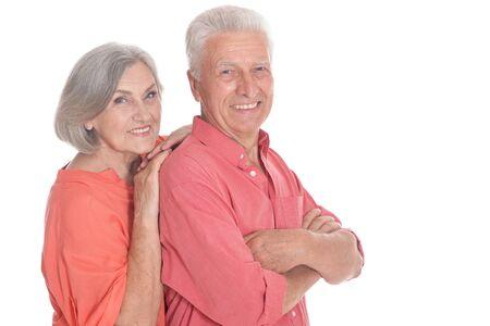 Smiling senior couple wearing bright clothing on white background