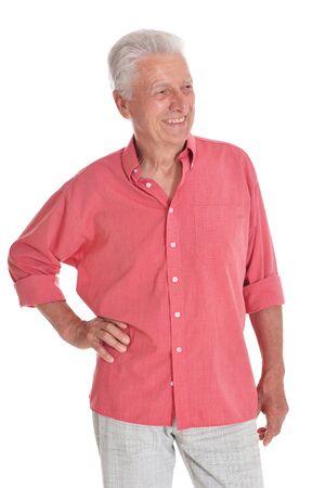 Smiling senior man wearing pink shirt holding hands on hips