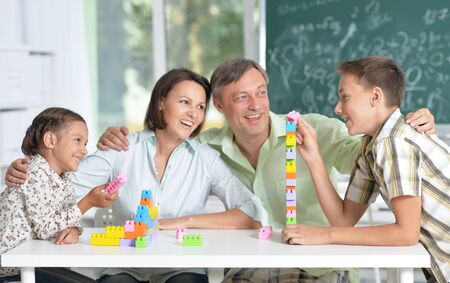 Portrait of parents and children playing with colorful plastic blocks at classroom Zdjęcie Seryjne