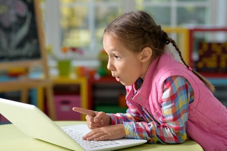 Portrait of concentrated little girl with laptop