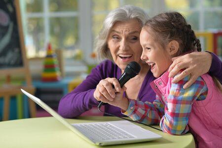 Portrait of grandmother and granddaughter singing karaoke