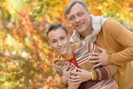Portrait of smiling father and son hugging in autumn park