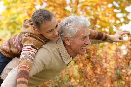 Porträt von Großvater und Enkel, die sich im Park umarmen