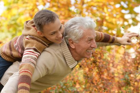 Portrait of grandfather and grandson hugging in park