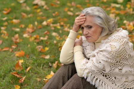 Portrait of beautiful sad senior woman on blurred autumn background