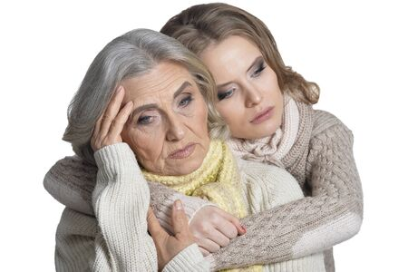 Close up portrait of senior mother and her daughter isolated on white background