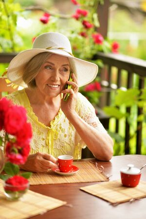 Portrait of a happy aged woman drinking coffee Banco de Imagens