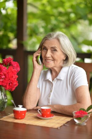 Portrait of a happy aged woman talking on smartphone
