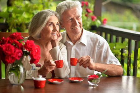Portrait of happy senior couple drinking coffee