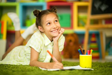 Portrait of cute smiling girl drawing at home Zdjęcie Seryjne