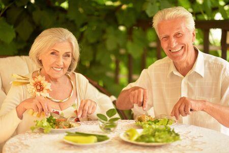 Ritratto di felice coppia senior cenando nel parco estivo