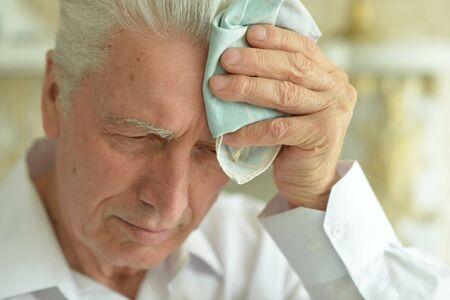 Portrait of senior man with headache at home
