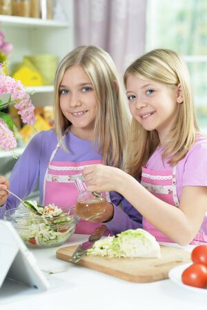 Two girls in pink aprons preparing salad Stockfoto