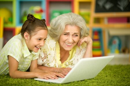portrait of happy grandmother and daughter using laptop Banque d'images