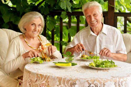 Portrait of happy senior couple having diner and posing on the veranda Stock Photo