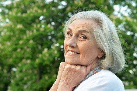 Portrait of smiling senior  woman posing in spring park 스톡 콘텐츠