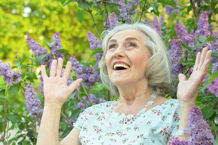 Portrait of happy senior beautiful woman on lilacs background