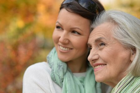 Portrait of senior woman with adult daughter in autumnal park
