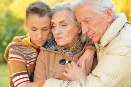 Portrait of sad grandfather, grandmother and grandson hugging