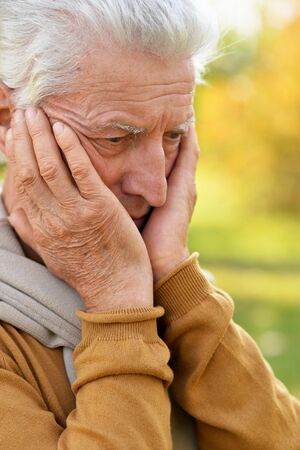 Sad senior man posing in autumn park 스톡 콘텐츠