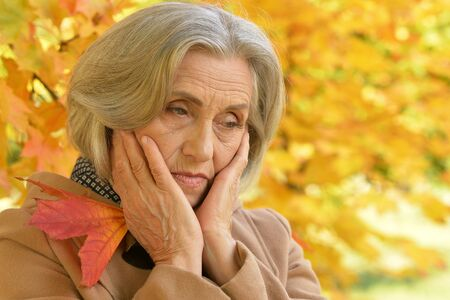Portrait of sad senior  woman in autumnal park Stok Fotoğraf