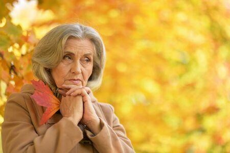 Portrait of sad senior woman in autumnal park