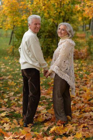 Portrait of happy mature couple posing outdoors in autumn park Banco de Imagens