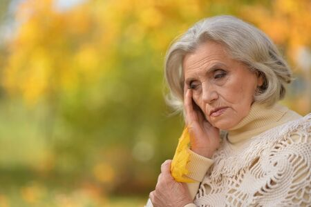 Beautiful sad senior woman on blurred autumn background
