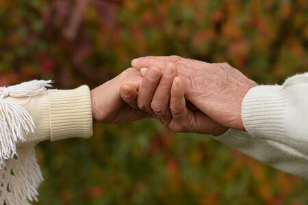 Portrait of couple holding hands together on background of park