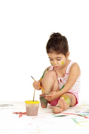 Portrait of lovely young girl draws painting while sitting on the floor