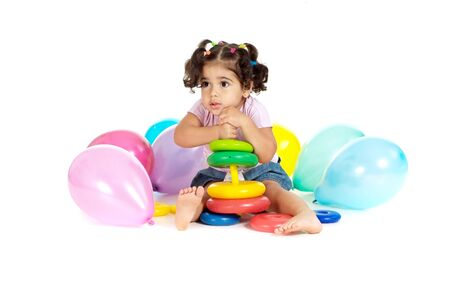 Portrait of girl with balloons and toys Imagens