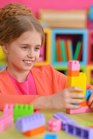 Curly little girl playing with colorful plastic blocks
