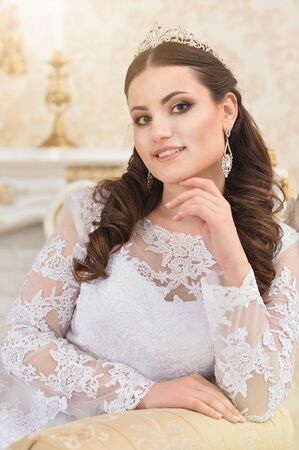 Portrait of young beautiful bride in white dress posing Imagens