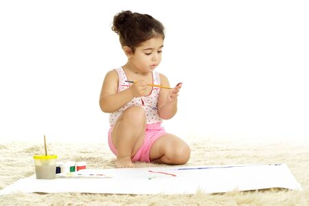 Portrait of cute girl draws paints on the floor on white background
