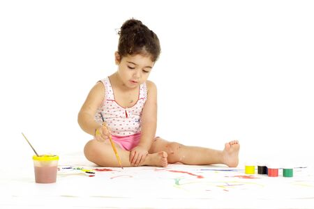 Portrait of pretty little girl painting picture on a white background Imagens