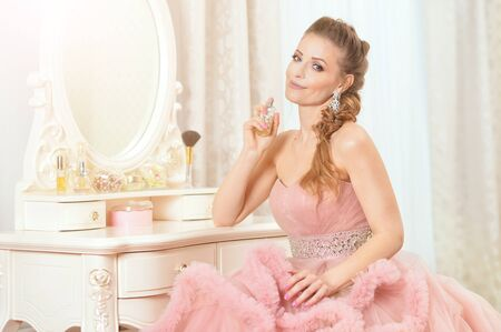 Portrait of beautiful young woman in pink dress with perfumes Imagens