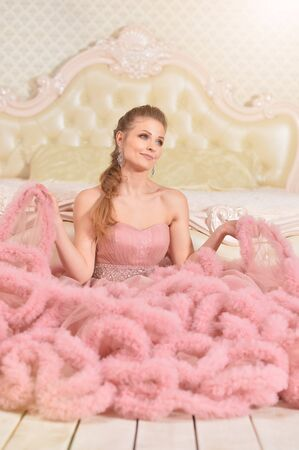 Portrait of beautiful young woman in pink dress posing in bedroom