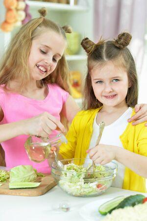 Portrait of cute girls preparing delicious fresh salad