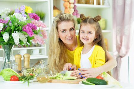 Portrait of smiling mother and daughter cooking together