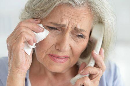 Portrait of upset senior woman calling doctor Banco de Imagens