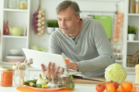 Portrait of elderly male chef using laptop